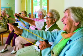 Large group of happy enthusiastic elderly ladies exercising in a gym sitting in chairs doing stretching exercises with rubber bands.