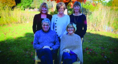 family sits together outside in nature for group photo