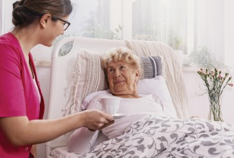 Senior in bed with caregiver